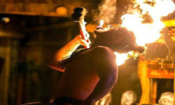 A close up of a Polynesian Dancer back lit by the high rising flames of fire torches held across his bare shoulder.