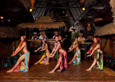 Five female Polynesian Dancers pose in a stylized pose wearing colorful traditional attire.