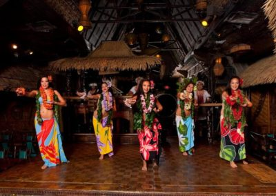 Five female Polynesian Dancers caught in mid-dance wearing colorful traditional attire.