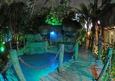 The romantic Mai-Kai boardwalk curving around the lagoon and waterfall illuminated in blue and green lights against the dark night sky.