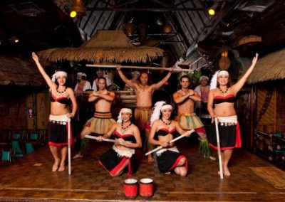 Polynesian Revue dancers in a theatrical group pose with musical instruments on the Mai-Kai stage.