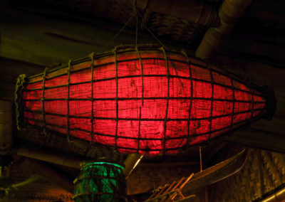 A close up of a nautical themed lantern with a warm red glow - one of many lanterns suspended from the Mai-Kai ceilings.