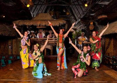 Five female Polynesian Dancers wearing colorful traditional attire with arms extended in a beautiful group pose.