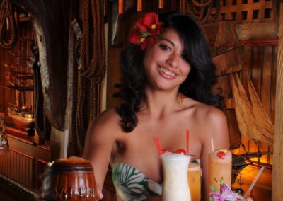 Sarong clad maiden serves the Mai-Kai classic Barrel O' Rum in signature barrel mug along with a tray of classic Mai-Kai cocktails.
