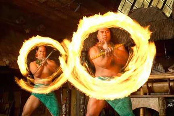 Two Male Polynesian fire dancers creating two simultaneous rings of fire with a dramatic flair.