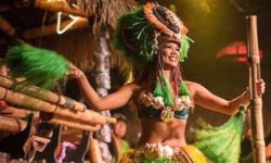 A female Polynesian dancer in a bright green costume performing on Mai-Kai's stage.