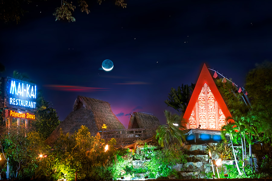 Gorgeous night view of the brightly lit Mai-Kai gardens and thatched roofs against the backdrop of stars and crescent moon.