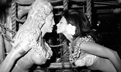 A Molokai maiden kissing the nautical figurehead in the shape of a woman in The Molokai Bar.