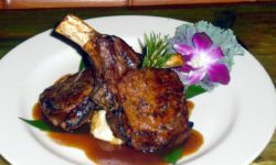 Succulent Pork chops served over mashed potatoes with orchid bloom.