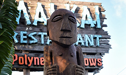 Authentic hand crafted wooden tiki sculpture offset by the signature wooden Mai-Kai sign and blue sky.